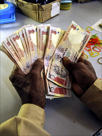 A bank employee counts currency notes at a cash counter in Agartala.