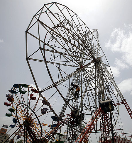 A worker dismantles a ferris wheel after the end of a fair in the western Indian city of Ahmedabad.