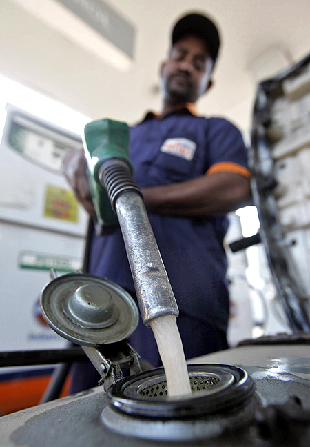 A worker fills petrol in a scooter at a fuel station in Kolkata