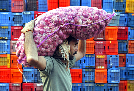 A labourer carries onions at a wholesale market in Mumbai.