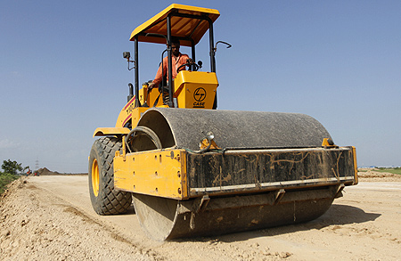 A worker drives a road-roller during road construction near the proposed Ford car plant in Sanand.