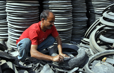 A worker dismantles a worn-out rubber tyre for recycling at a workshop in Srinagar.