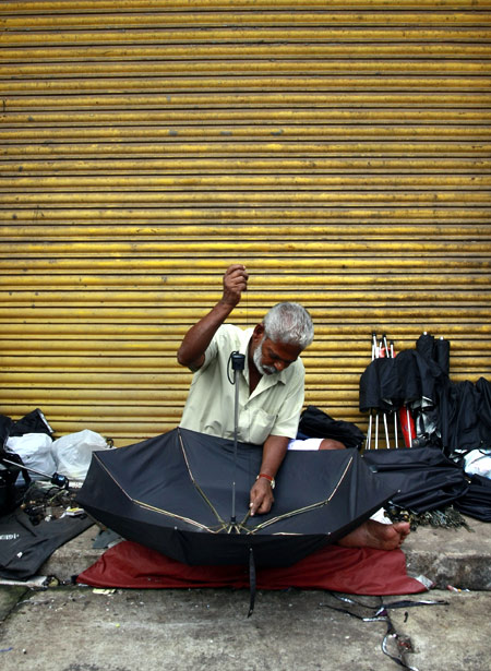 A man repairs an umbrella at his roadside stall in Kochi.
