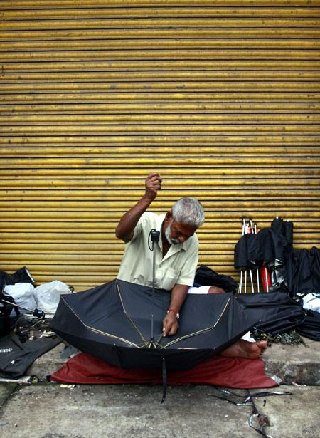 A man repairs an umbrella at his roadside stall in Kochi.