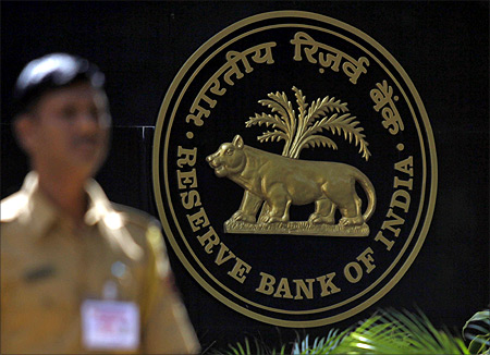 A policeman walks past the logo of the Reserve Bank of India (RBI) outside its head office in Mumbai.