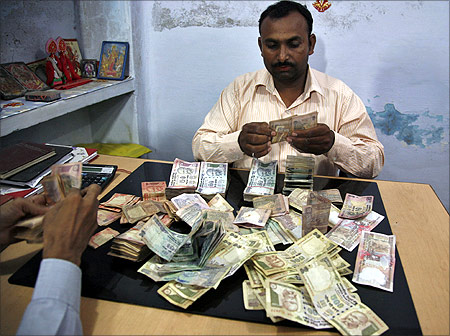 Employees at a wholesale shop count money in Allahabad.
