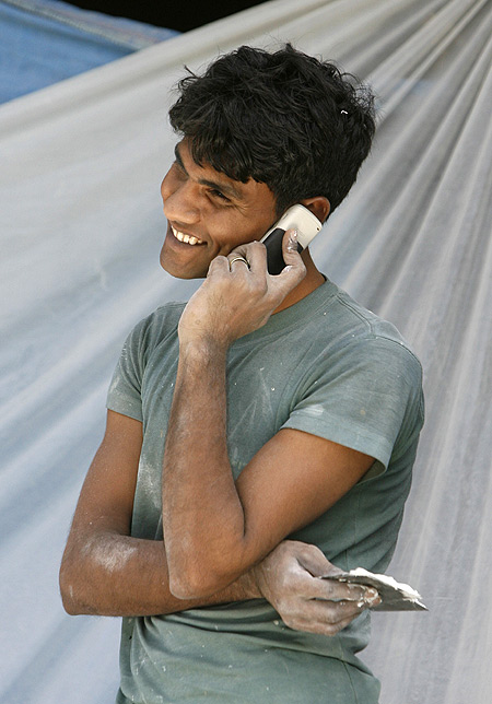 A labourer talks on his mobile phone at a construction site in New Delhi.