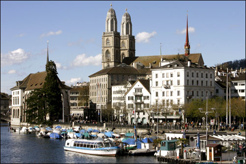 People walk along the Limmat River in front of the Grossmuenster church in the Swiss city of Zurich.