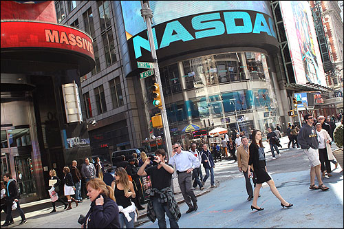 Pedestrians walk past the Nasdaq stock market at Times Square.