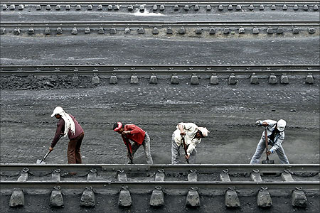 Men work inside a coal yard as they clear coal from a railway track near Ahmedabad.