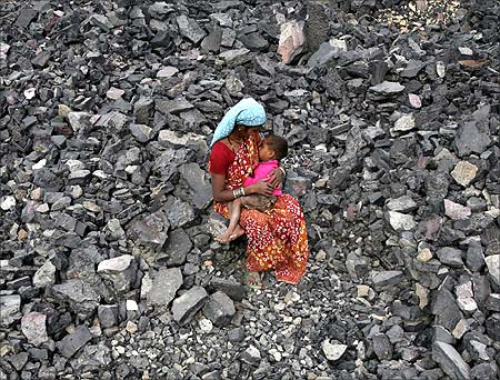 A worker breastfeeds her child during lunch break at a coal yard in Jammu.