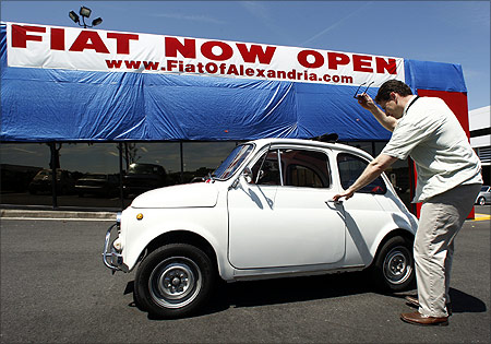 Mark Santaw of Woodbridge, Virginia, gets out from his 1971 Fiat 500 in front of a newly opened Fiat dealership in Alexandria, Virginia.