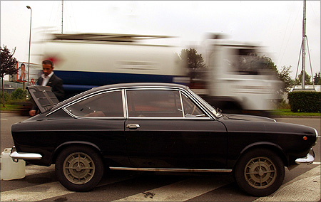 A truck drives by as Marco Santin attempts to fix his Fiat 850 Special which broke down on a roadside in central Milan.