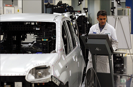 An employee of Fiat performs a quality control check on the new Panda car at the Fiat plant in Pomigliano D'Arco, near Naples.