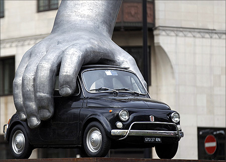 A Fiat 500 gripped by an aluminum hand is seen in Italian artist Lorenzo Quinn's sculpture Vroom Vroom in London.