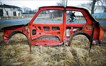A cyclist is seen through a part of a Fiat 126 car, nicknamed