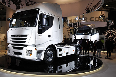 Visitors walk along a display of heavy trucks at the Fiat Iveco exhibition area during a preview day at the IAA commercial vehicles trade fair in Hanover.