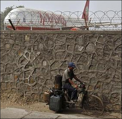 A cyclist rides past a perimeter wall at Mumbai's domestic airport, behind which a decommissioned Kingfisher Airlines aircraft is parked.