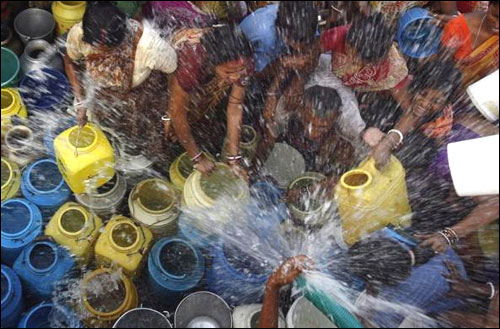 Residents of a slum collect drinking water from a tanker.