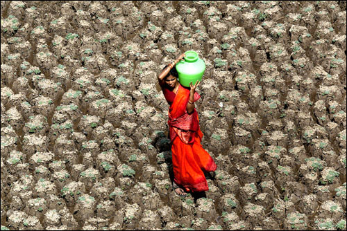 A woman carries a pot of water home, taking a short cut across the dry bed of the Usmansagar lake, in Hyderabad, capital of the south Indian Andhra Pradesh state, June 6, 2003.