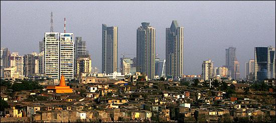 High rise buildings are seen behind a slum in Mumbai.
