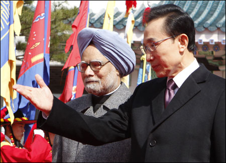 South Korean President Lee Myung-Bak (R) and India's Prime Minister Manmohan Singh walk to attend official