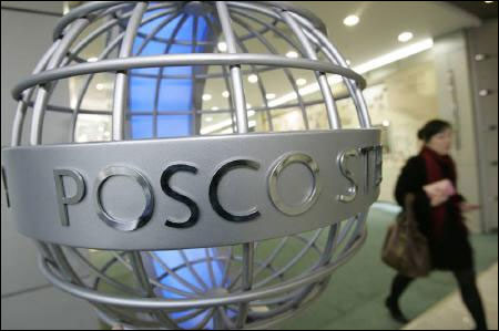 A woman walks past a sculpture of POSCO's logo at its headquarters in Seoul.