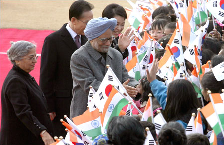 Prime Minister Manmohan Singh(C) and his wife Gursharan Kaur (L) greet South Korean children during a welcoming ceremony held at the Presidential house.