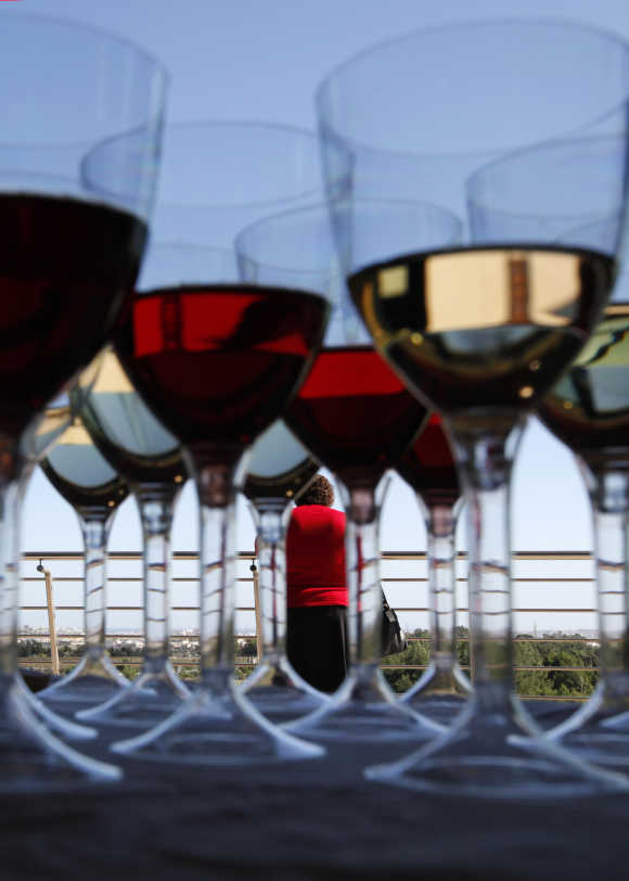 A woman attends the Vivanda Taste the Med food festival as glasses of red and white wine are placed on a display table at Ta Qali, outside Valletta, Malta.