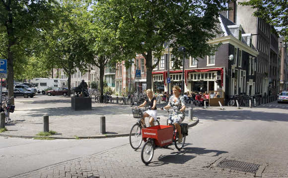 Two women ride their bicycles on the Lindengracht in Amsterdam.