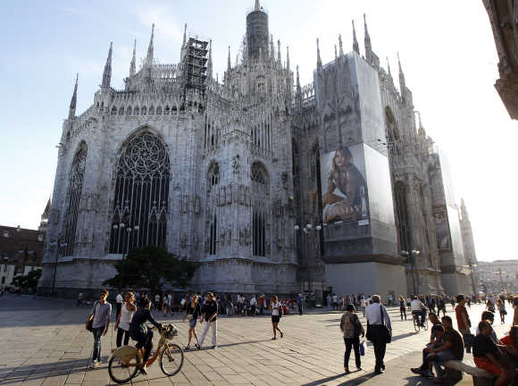 An advertisement for Burberry is seen on Duomo cathedral as people walk across Duomo square in Milan, Italy.