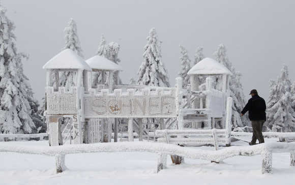 A man walks past a snow and ice covered children's playground at the peak of the Feldberg mountain in Koenigstein, 30km west of Frankfurt.