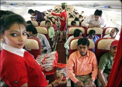 Stewardesses serve passengers inside a Kingfisher Airlines aircraft.
