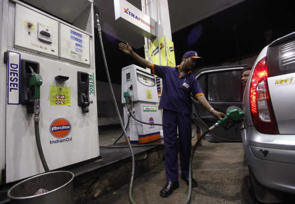 A worker fills a car with petrol.