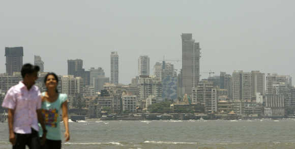 A couple walk at the seafront in Mumbai.
