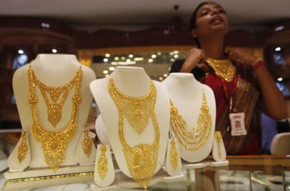 A saleswoman displays a gold necklace at a jewellery showroom in Kolkata.
