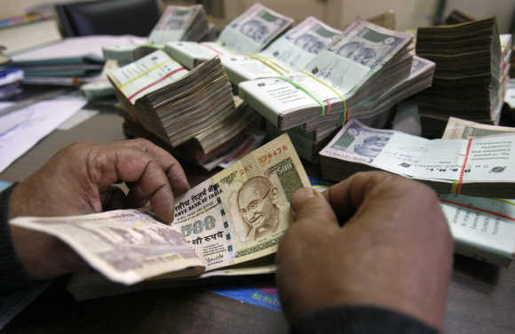 An employee counts currency notes at a cash counter inside a bank in Agartala.