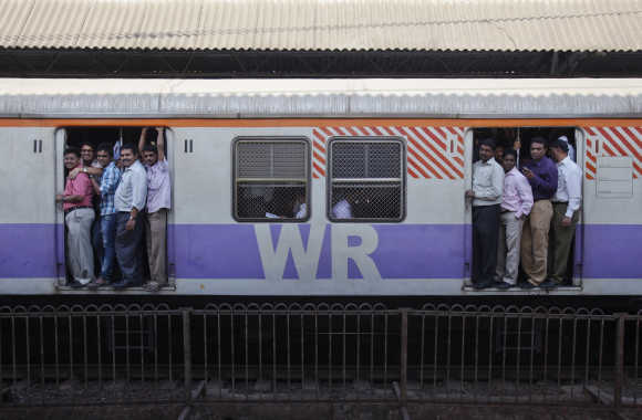 Passengers ride a commuter train in Mumbai.