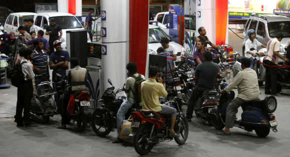Motorists wait at a fuel station to fill petrol in Ahmedabad.