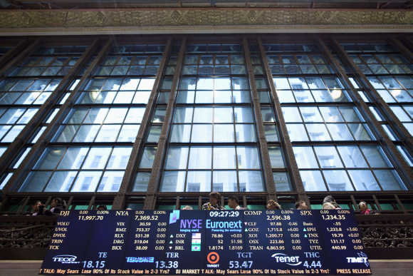Visitors stand on a balcony overlooking the floor of the New York Stock Exchange in New York.