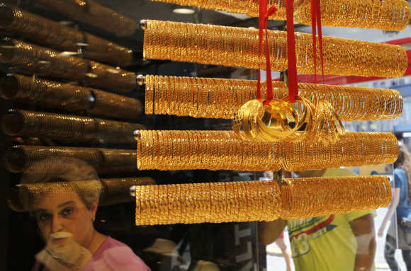 A customer is reflected in the window of a jewellery shop where gold bangles are on display in Istanbul, Turkey.