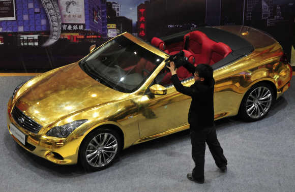 A man films a gold-plated Infiniti G37 at a jewelry store in Nanjing, Jiangsu province, China.