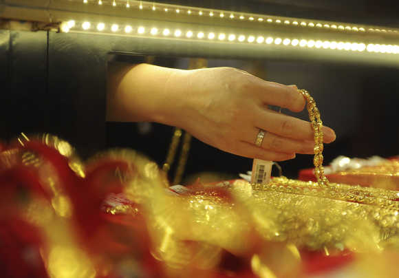 An employee arranges gold jewellery at the counter of a gold shop in Hefei, Anhui province, China.