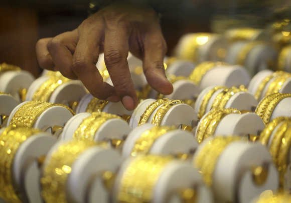 A Nepalese jewellery store keeper arranges gold jewellery in Kathmandu.