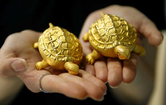 An employee holds replicas of turtles made of gold during a photo opportunity at a jewellery shop in Seoul.