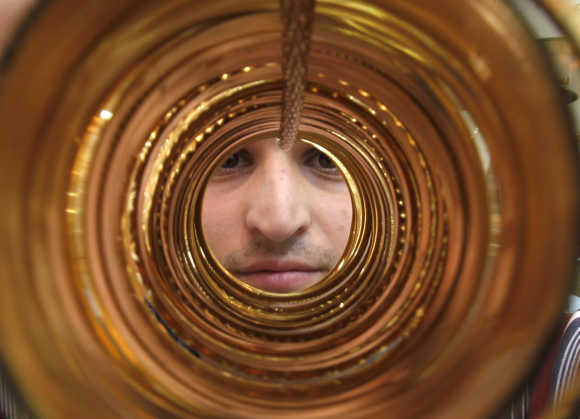 A goldsmith poses with gold bangles in his jewellery shop in Amman's gold market.