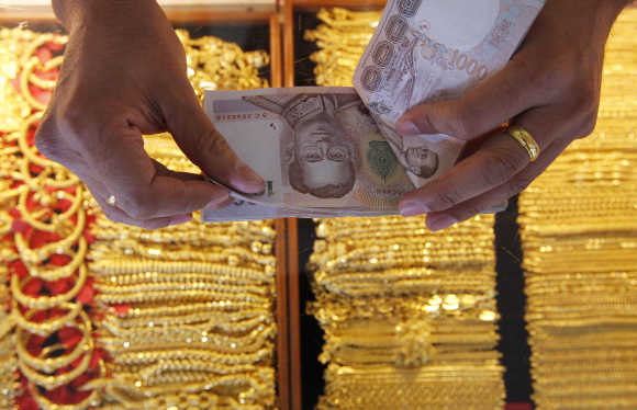 A shopkeeper counts Thai baht banknotes as he buys gold from a customer in Bangkok's Chinatown.