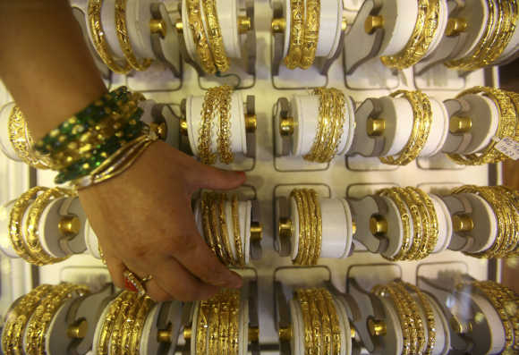 A Nepalese jewelry store keeper arranges gold jewellrey in Kathmandu.