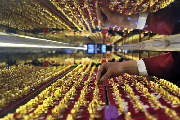 A vendor arranges gold rings on display at a jewellery shop in Shenyang, Liaoning province, China.