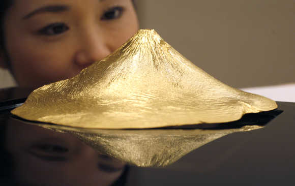 Pure gold artifact shaped as Japan's Mount Fuji by Japanese jewellery maker Ginza Tanaka is displayed during an unveiling in Tokyo.